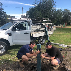 2 men installing water fountains in a park